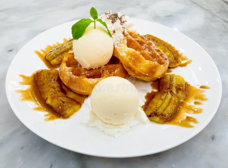 Belgische wafel met roomijs en geroosterde die banaan met honing wordt bedekt stock afbeelding