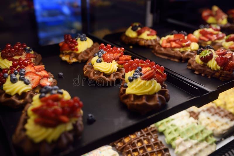 Belgische wafels met chocolade, bessen, zoete saus, room stock afbeeldingen