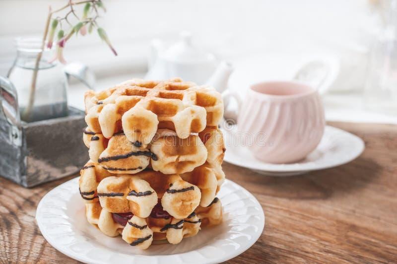 Belgische Waffeln der neuen Runde mit einer Schicht Stau gegossen mit Schokolade auf einer weißen Platte mit einer Tasse Tee Absc stockbild