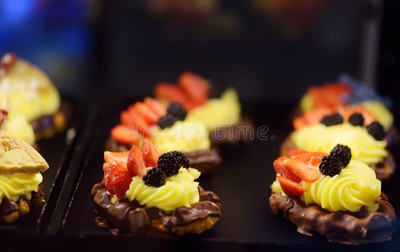 Belgische Waffeln mit Schokolade, Beeren, süße Soße, Creme stockfoto