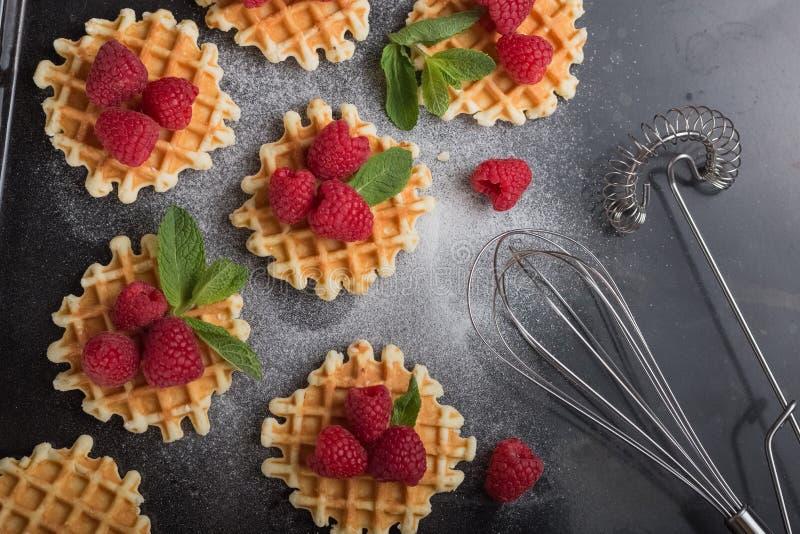 Belgiska dillandear med hallon på den svarta tabellen med sockerpulver Dekorerat med mintkaramellsidor sund frukost arkivbild