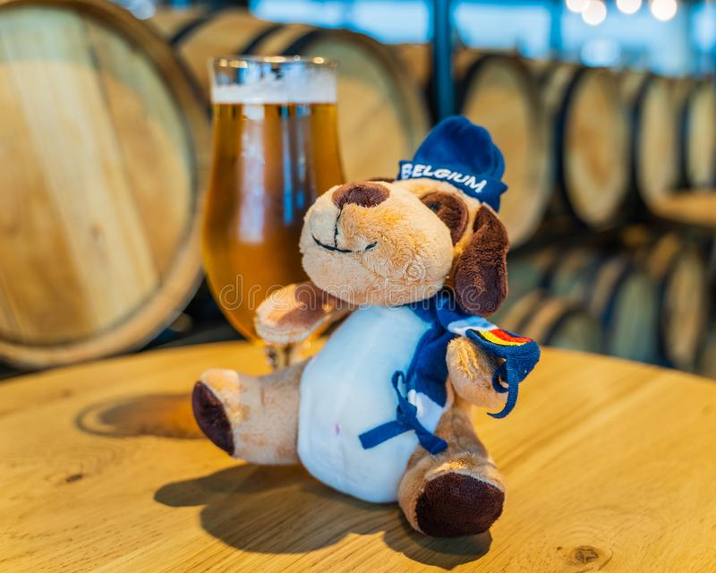 Belgium beer and plush mascot with blurred wooden barrels in background royalty free stock photography