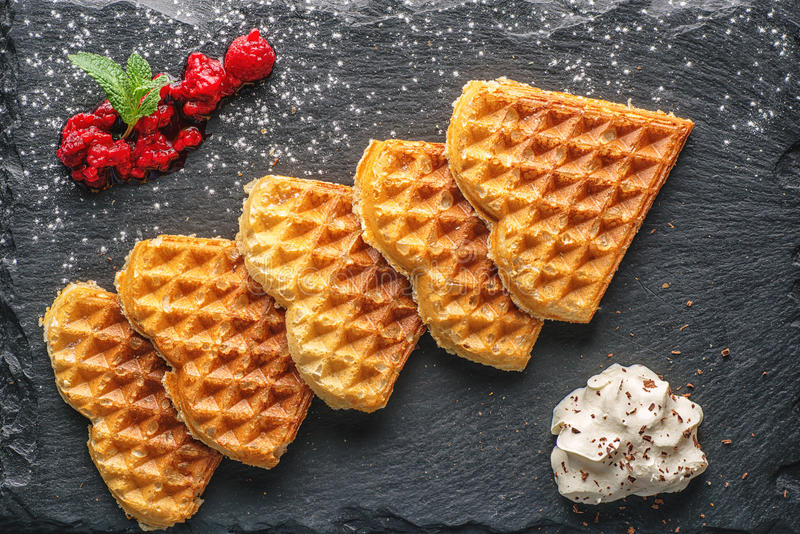 Belgium waffle with heart shape topped with chocolate topping, whipped cream and fresh raspberries on top, product photography for royalty free stock photography