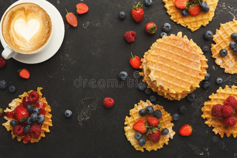 Round belgium waffles with berries, tasty breakfast on black background stock photo