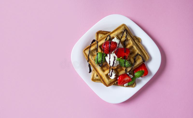 Belgium waffles dessert with strawberries, ricotta cheese and chocolate on pink background. Belgium waffles dessert with strawberries, basil, ricotta cheese and stock images
