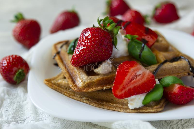 Belgium waffles dessert with strawberries, ricotta cheese and chocolate. Selective focus. Belgium waffles with strawberries, ricotta cheese and chocolate on stock photography