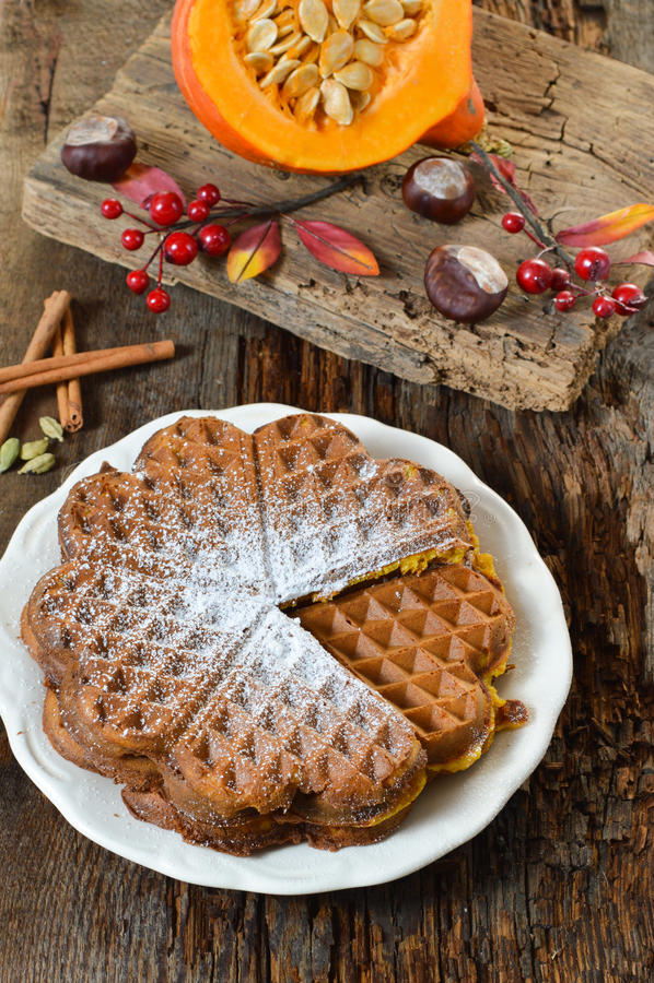 Belgium waffles with pumpkin. Autumn Belgium waffles. Pumpkin Belgium waffles on a plate in the background of an old board royalty free stock image