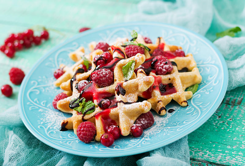 Belgium waffles with raspberries and syrup royalty free stock photos