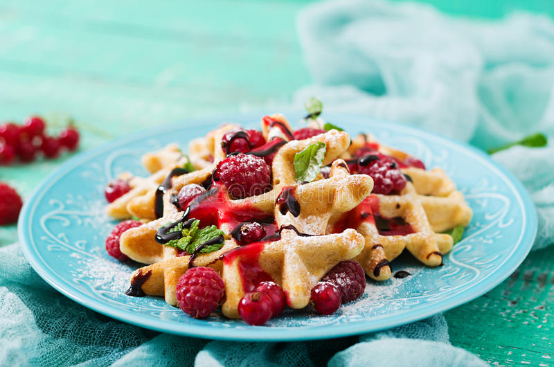 Belgium waffles with raspberries and syrup royalty free stock image