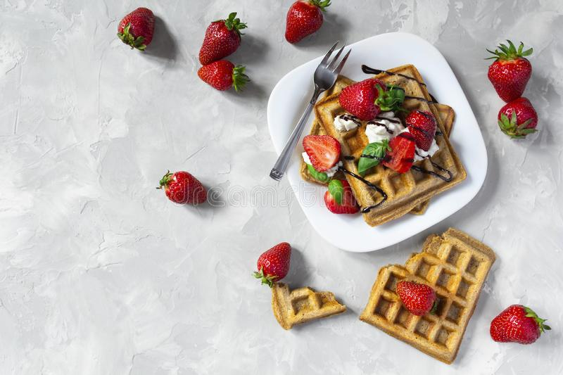Belgium waffles with strawberries, ricotta cheese and chocolate on white plate. Top view. Copy space. Belgium waffles with strawberries, basil, ricotta cheese royalty free stock photography