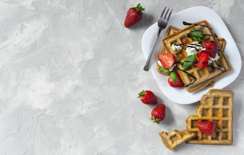 Belgium waffles with strawberries, ricotta cheese and chocolate on white plate. Top view. Copy space. Belgium waffles with strawberries, basil, ricotta cheese stock photos