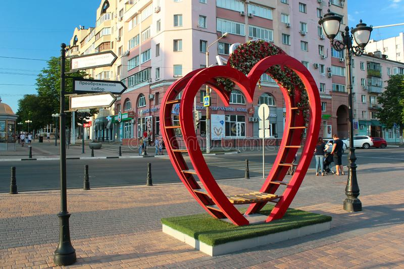 Symbolic heart-shaped bench of love in Belgorod, Russia. Belgorod, Russia - June 22, 2019: Symbolic heart-shaped bench of love and flower pots on pedestrian stock photos