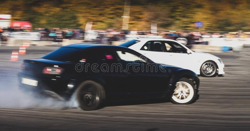 A drift racing car in action with smoking tires in show. Belgorod , Russia - OCT 13, 2018: A drift racing car in action with smoking tires in show stock photography