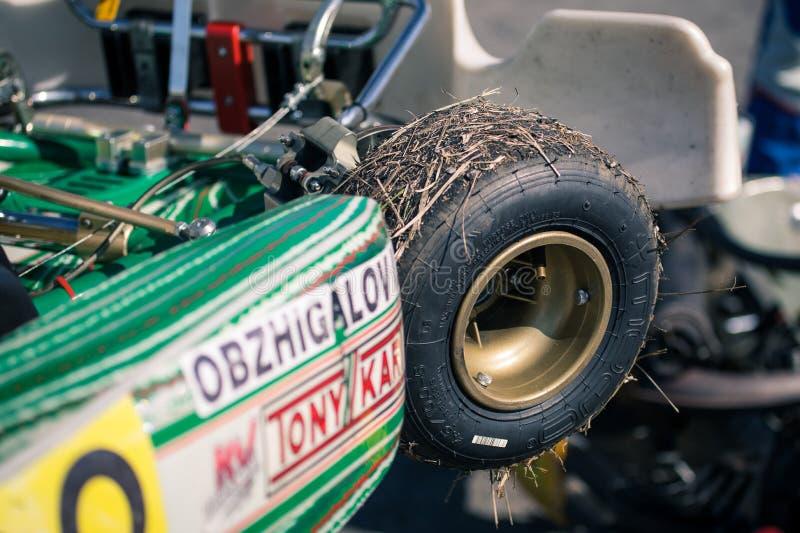 Belgorod Ryssland - Augusti 13: klibbat torrt gräs i hjul, oidentifierade piloter konkurrerar på spåret på sportarna som karting arkivbilder