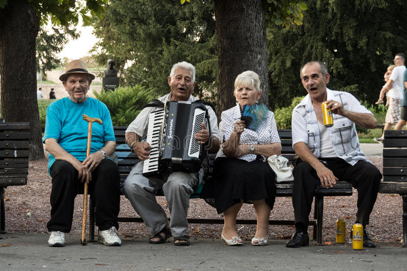 BELGRADE, SERBIA - AUGUST 30, 2015: Serbian old people celebrating, playing accordeon and drinking local beer stock images