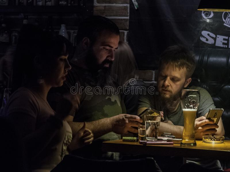 Two young bearded men, white caucasian males, drinking beer in a pub bar while looking at the internet on smartphones. BELGRADE, SERBIA - MARCH 17, 2018 stock photo