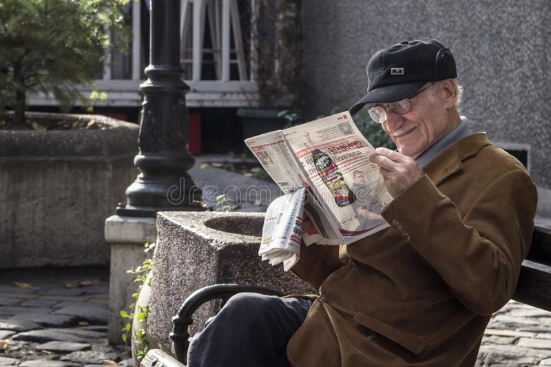 Old Man, happy, sitting on a bench, reading a Serbian newspaper whilebeing relaxed in a street of the center of Belgrade royalty free stock photos