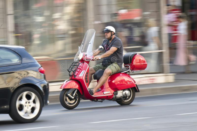 One mature man in shorts and t shirt riding a red vintage vespa scooter in the city street traffic royalty free stock photo