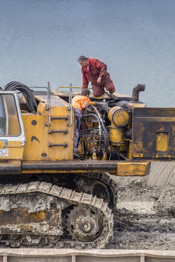 Repairmans repairing engine of excavator stock images
