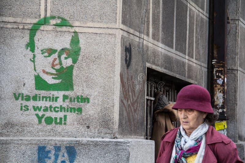 BELGRADE SERBIEN - NOVEMBER 7, 2014: Den gamla kvinnan som förbigår en pro-rysk grafitti Vladimir Putin, håller ögonen på dig i B royaltyfri bild