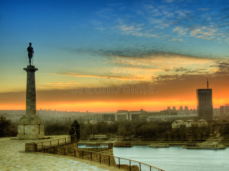 Belgrade at sunset. A view of a beautiful golden sunset over the city of Belgrade, Serbia with the Monument of Pobednik in the foreground stock photo