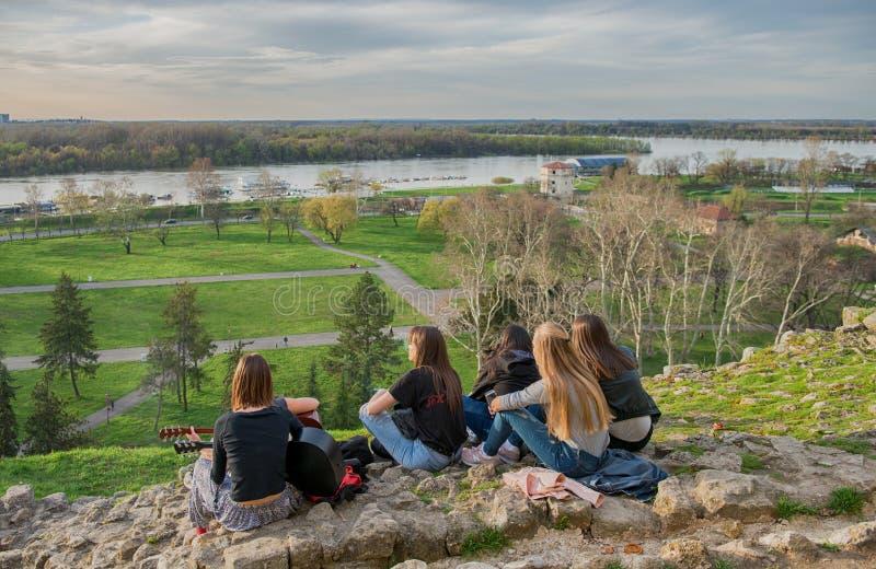 BELGRADO, SÉRVIA - EM ABRIL DE 2018: As meninas apreciam a opinião da cidade do monte em Belgrado Kalemegdan foto de stock