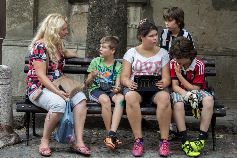 BELGRADO, SERBIA - 2 AGOSTO 2015: Famiglia, compreso un adolescente, sedentesi su un banco e guardante una compressa fotografie stock libere da diritti