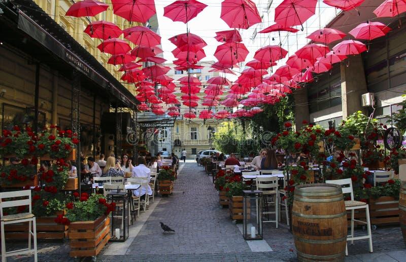 BELGRADO, SERBIA 6 DE JUNIO DE 2019: Paraguas rojos sobre el restaurante al aire libre en la calle Belgrado, Serbia de rey Peter imágenes de archivo libres de regalías