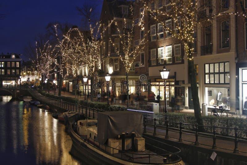 Belichtete Bäume und alte Fassaden in Amsterdam lizenzfreie stockfotografie