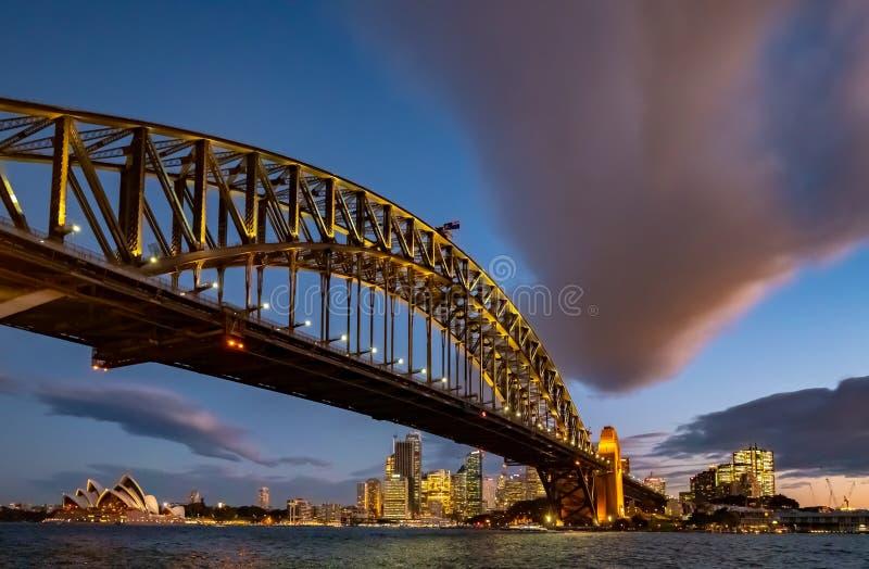 Belichtete Hafen-Brücke und Sydney Opera House bei Sonnenuntergang mit einer drastischen Wolke stockfotos