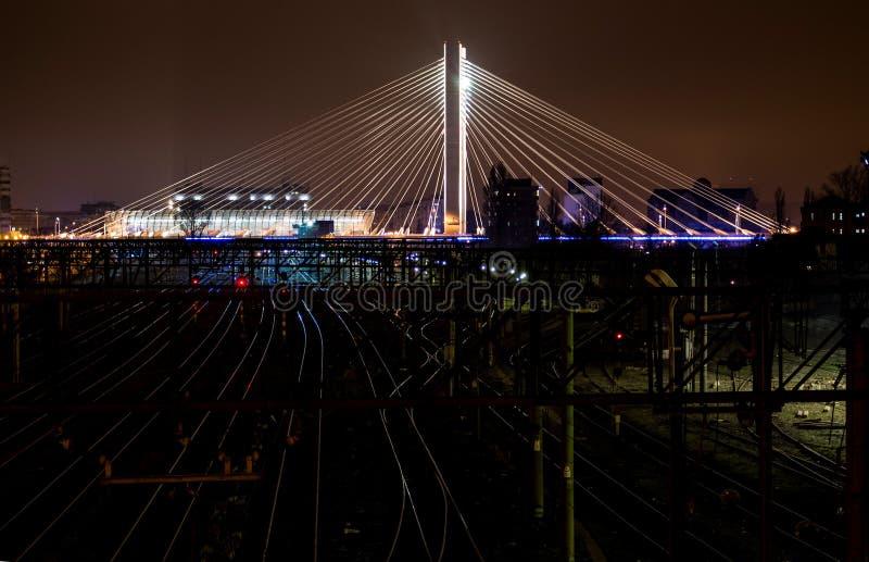 Belichtete Schrägseilbrücke über städtischem modernem Bahnmarkstein stockbilder