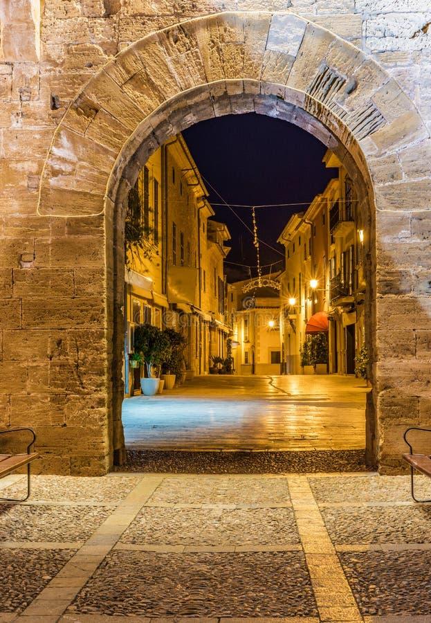 Belichtete Straße mit historischem Festungsmauertor an der alten Stadt von Alcudia auf Majorca, Spanien stockfotos