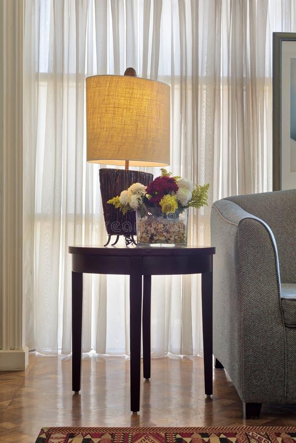 Belichtete Tischlampe und bunter Blumenpflanzer auf kleinem dunkelbraunem Holztisch auf Hintergrund des weißen Vorhangs stockfotos