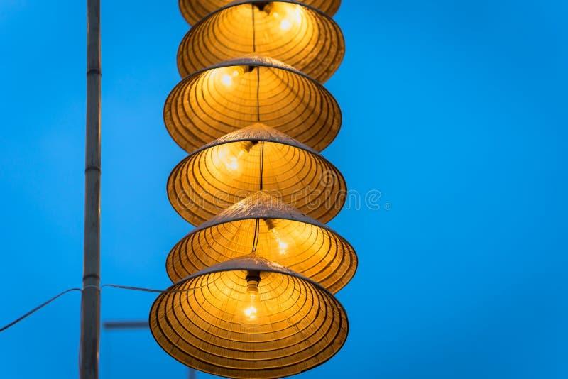 Belichtete vietnamesische traditionelle konische Hüte des Streifens, die in der Dämmerung am Draht für Dekoration, mit blauem Him stockbilder