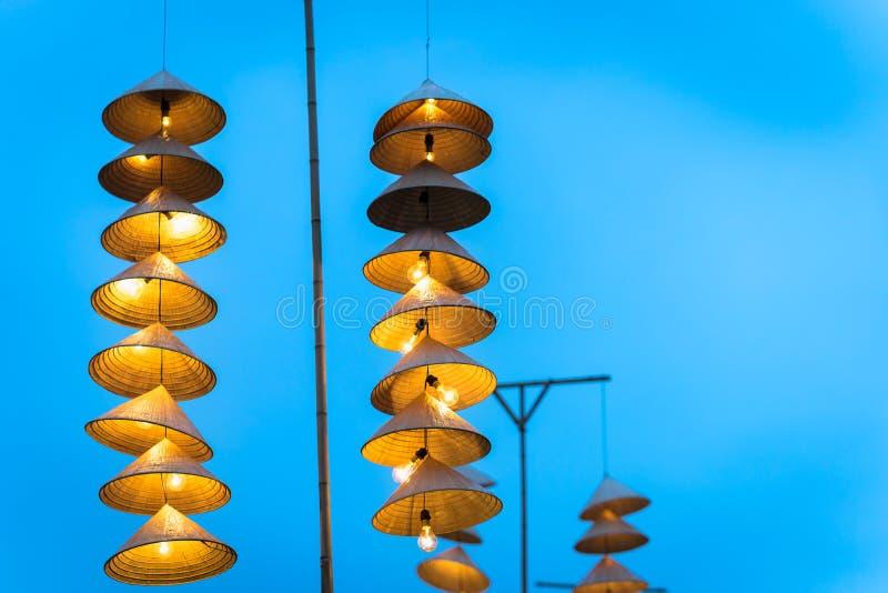 Belichtete vietnamesische traditionelle konische Hüte des Streifens, die in der Dämmerung am Draht für Dekoration, mit blauem Him lizenzfreies stockbild
