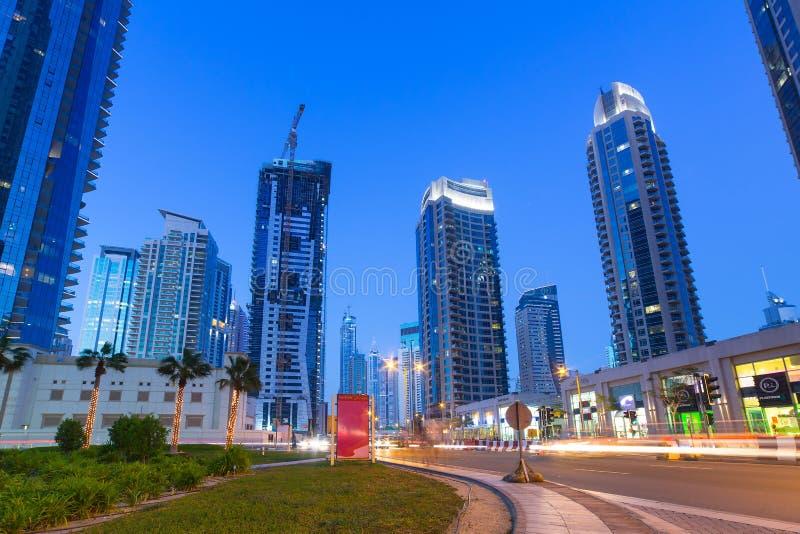 Belichtete Wolkenkratzer von Dubai-Jachthafen nachts lizenzfreie stockfotos