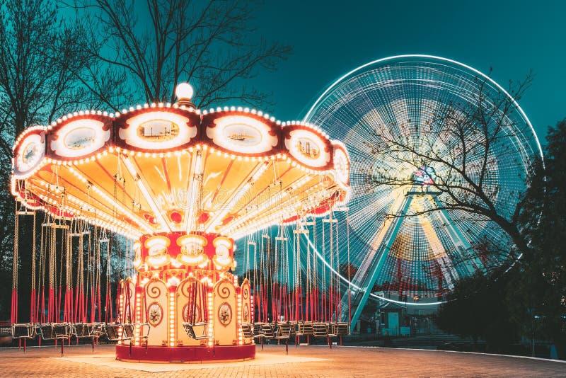Belichtetes Anziehungskraft-Ferris Wheel And Carousel-Karussell am Sommer-Abend im Stadt-Vergnügungspark stockbild