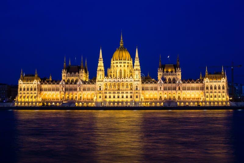Belichtetes Budapest-Parlamentsgebäude an der Nacht mit bewölktem Himmel und an der Reflexion in der Donau stockbild