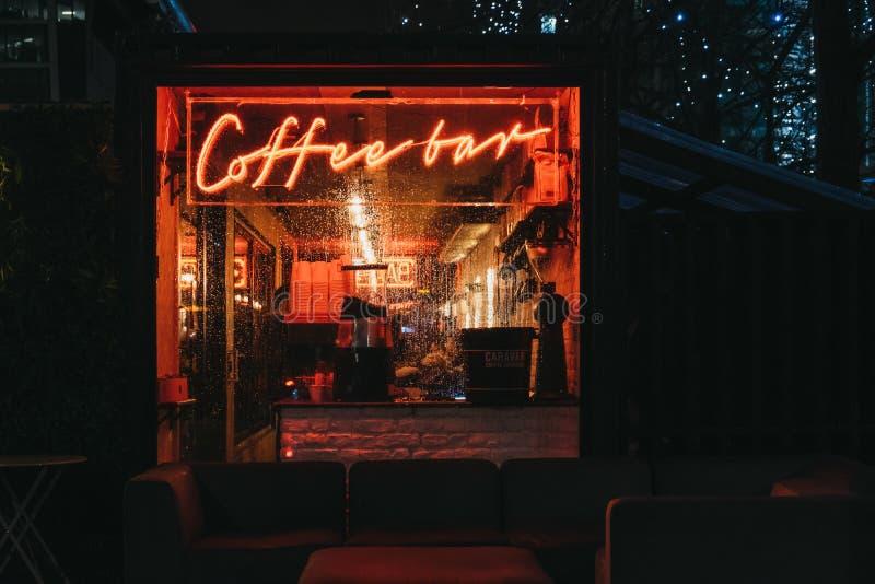 Belichtetes Fenster und Leuchtreklame auf einem Café in Canary Wharf, London, Großbritannien lizenzfreie stockbilder