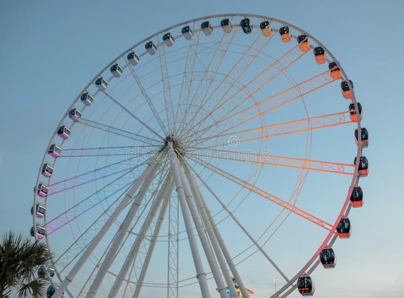 Belichtetes Riesenrad an der Dämmerung auf einem blauen Himmel mit Palmen stockbild