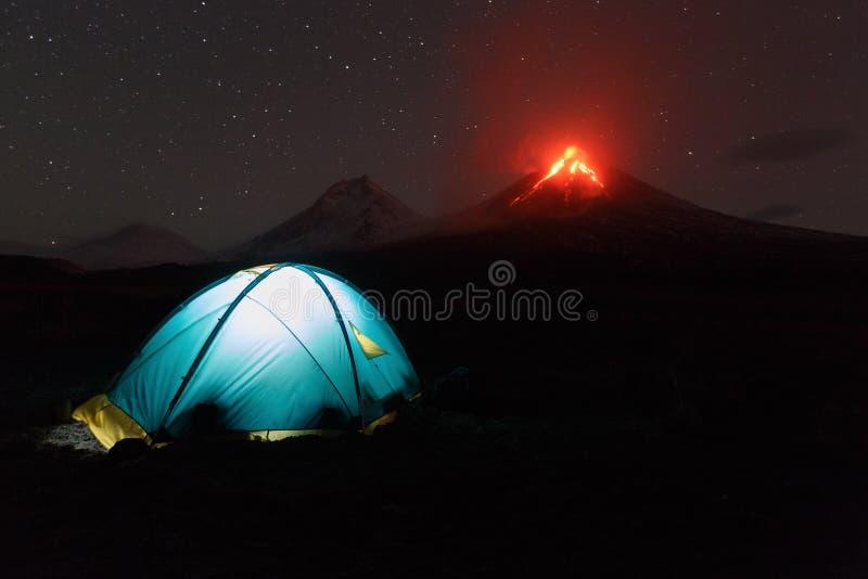 Belichtetes touristisches Zelt nachts auf dem Hintergrund, der Vulkan ausbricht stockfotografie