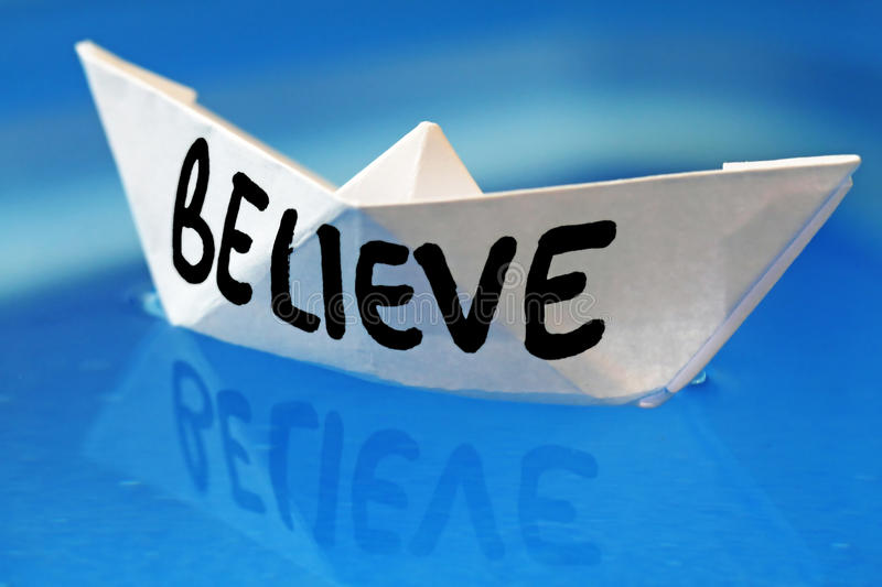 Believe. Paper boat on cyan background stock image