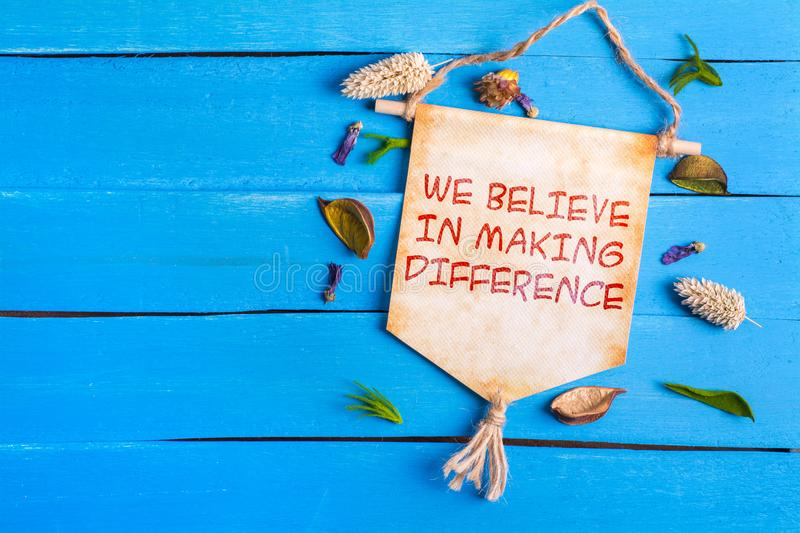 We believe in making difference text on Paper Scroll. With dried flower around and blue wooden background royalty free stock images