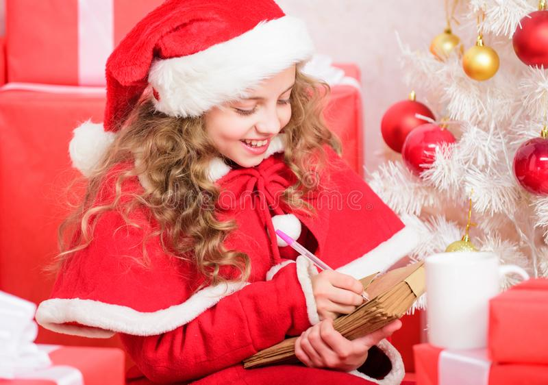 Believe in miracle. Letter for santa. Wish list. Child santa costume enjoy christmas eve. Girl little kid hold pen and royalty free stock photo