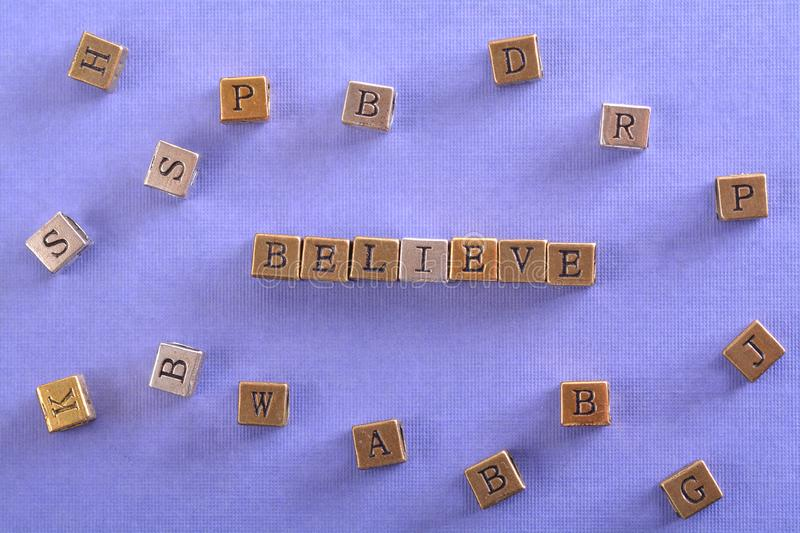 Believe word metal block. Believe word gold and silver metal block on blue paper with letter blocks around royalty free stock images
