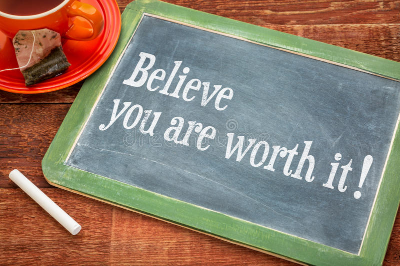 Believe you are worth it. Motivational advice on a slate blackboard with chalk and cup of tea royalty free stock images