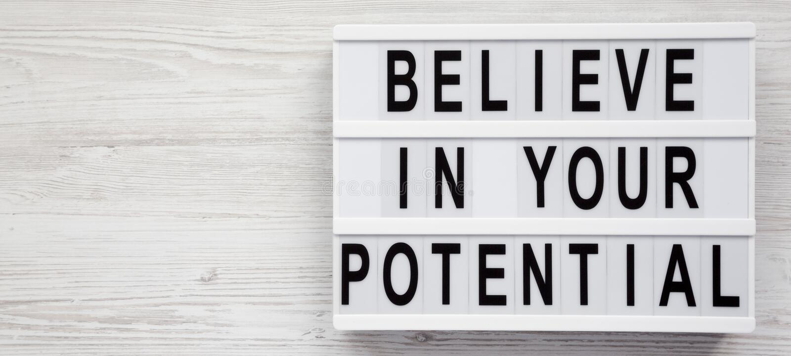 `Believe in your potential` words on a lightbox on a white wooden surface, top view. Space for text stock photos