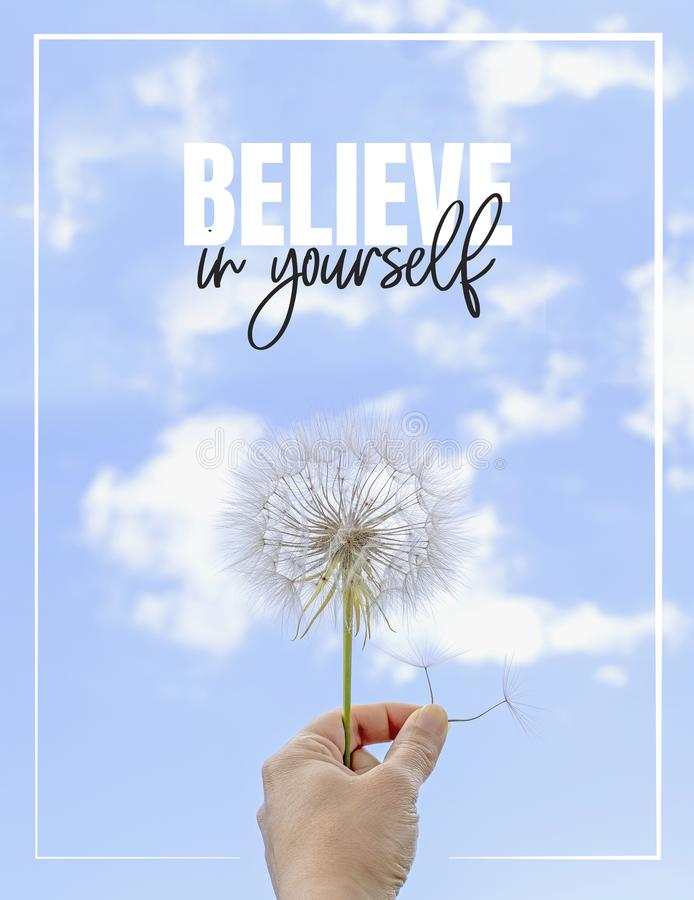 Believe in yourself, Hand holding Dandelion flower pointing to blue sky, close up photography, banner design. Poster design. Positive, motivational royalty free stock image