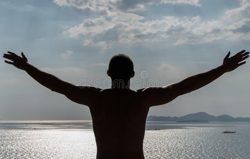 Believe in yourself. Man standing with hands wide open stock photo