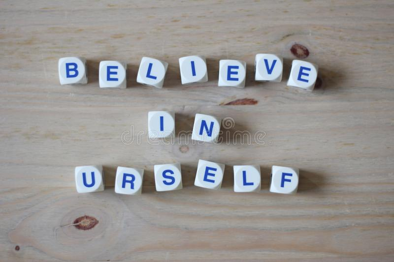 Believe in yourself. Believe in urself letters cube wordings on wood background royalty free stock photo